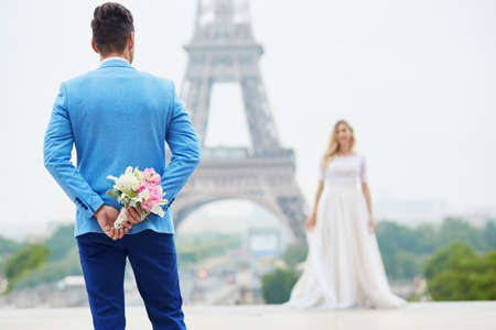 Groom hiding the wedding bouquet behind his back and going to offer it to a bride. Romantic wedding couple near the Eiffel tower in Paris. Surprise proposal concept Stock Photo