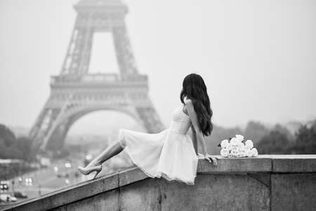 Elegant Parisian woman in pink tutu dress with white roses sitting near the Eiffel tower at Trocadero view point in Paris, France, black and white image Stock Photo