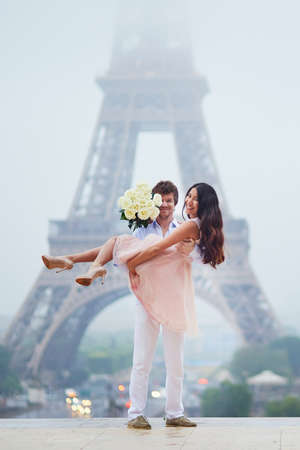 Beautiful romantic couple in love with bunch of white roses having fun near the Eiffel tower in Paris on a cloudy and foggy rainy day