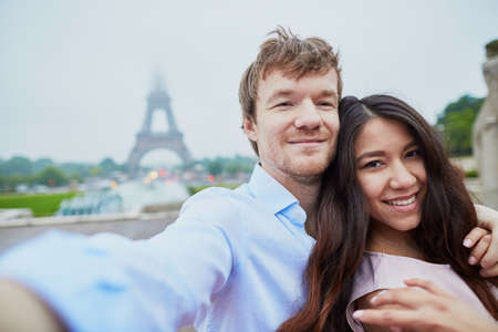 Beautiful romantic couple in love taking selfie near the Eiffel tower in Paris on a cloudy and foggy rainy day