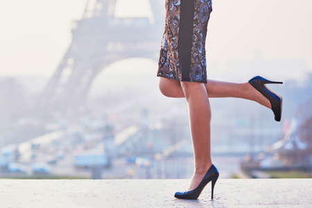 Woman wearing high heels shoes and walking near the Eiffel tower at early morning in Paris, closeup of legs Zdjęcie Seryjne
