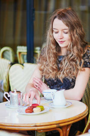 Beautiful Parisian woman in cafe, drinking coffee and eating macaroons, traditional French dessert Stock Photo