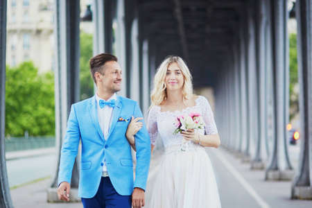 Just married couple in Paris, France. Beautiful young bride and groom on Bir-Hakeim bridge. Romantic wedding concept
