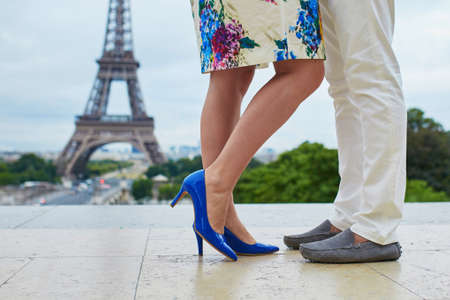 french kiss: Romantic French couple having a date near the Eiffel tower. Closeup of mans and womans legs during a kiss or hug. Unrecognizable lovers in Paris. Tourists enjoying vacation in France Stock Photo