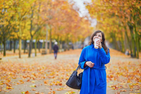 Beautiful young woman in Paris on a fall day with tea or coffee to go Stock Photo