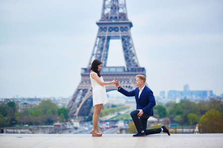 suddenness: Romantic engagement in Paris, man proposing to his beautiful girlfriend near the Eiffel tower. Surprise proposal or elopement concept Stock Photo