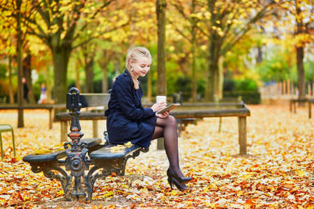 Beautiful young woman in the Luxembourg garden of Paris on a fall day, drinking coffee to go and reading book Stock Photo