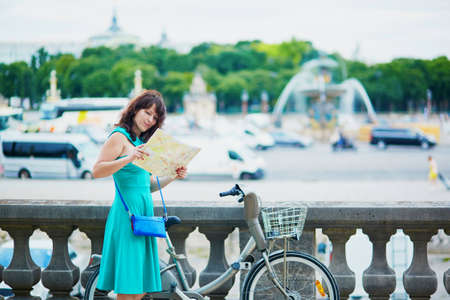 itinerary: Cheerful young woman riding a bicycle on a street of Paris and using map planning itinerary Stock Photo