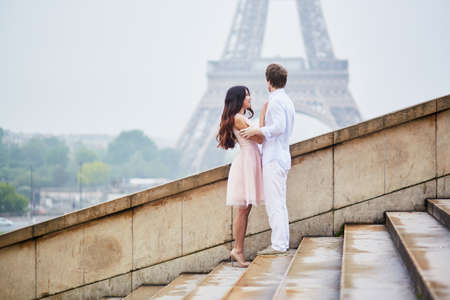 Beautiful romantic couple in love near the Eiffel tower in Paris on a cloudy and foggy rainy day Stock Photo