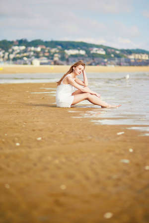 Beautiful young woman enjoying her vacation by ocean or sea, sitting near water edge at sunset. People on sea vacation concept Stock Photo