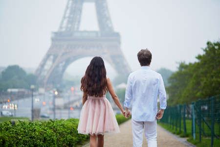 Beautiful romantic couple in love near the Eiffel tower in Paris on a cloudy and foggy rainy day, back view Stock Photo
