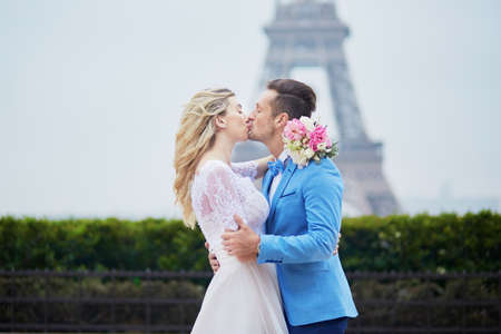 Just married couple near the Eiffel tower on their wedding day. Bride and groom in Paris, France Stock Photo