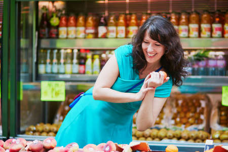 produce departments: Beautiful French woman choosing ripe organic peaches on a Parisian local market. Customer in food store, supermarket or hypermarket concept