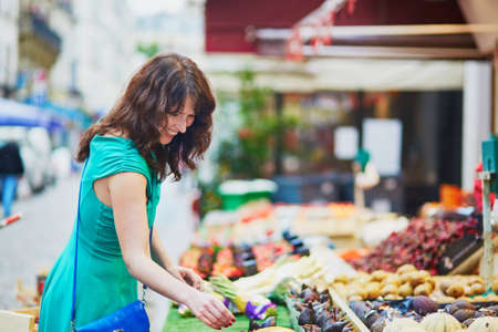 french woman: Beautiful French woman choosing ripe organic fruits on a Parisian local market. Customer in food store, supermarket or hypermarket concept Stock Photo
