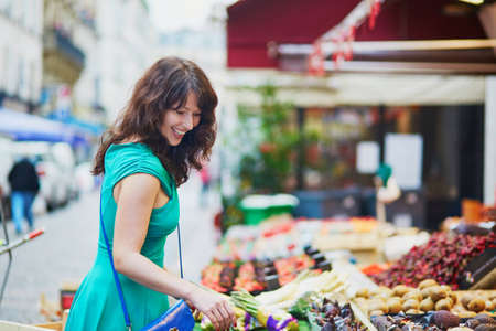 french woman: Cheerful happy young French woman selecting fruits on market in Paris, France Stock Photo