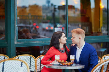 Happy couple drinking coffee in an outdoor cafe in Paris. Tourists enjoying their vacation in France. Romantic date or traveling couple concept