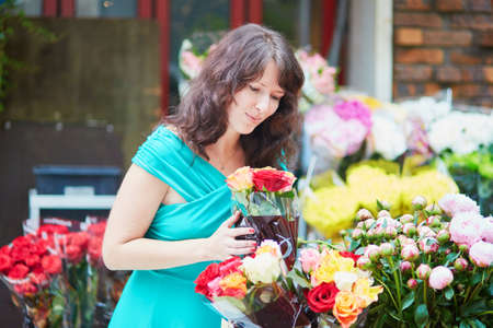 french woman: Beautiful French woman choosing flowers on a Parisian local market
