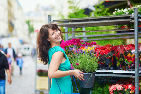 french woman: Beautiful French woman choosing lavender on a Parisian local market Stock Photo