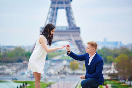 exaltation: Romantic engagement in Paris, man proposing to his beautiful girlfriend near the Eiffel tower. Surprise proposal or elopement concept Stock Photo