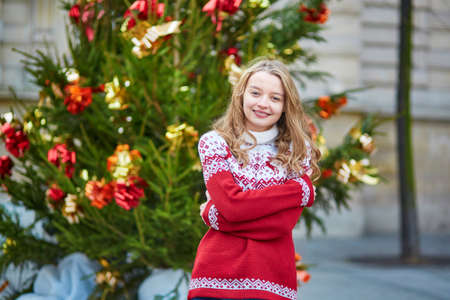 french model: Girl with a brightly decorated Christmas tree in Paris