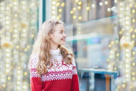 shopfront: Young girl looking at Parisian shop-windows decorated for Christmas