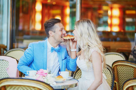Just married couple in traditional Parisian cafe drinking coffee and eating croissants. Bride and groom on their wedding day in a restaurant