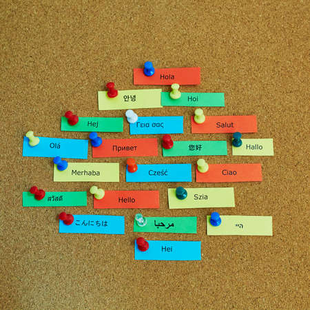 localization: Word Hello written in different languages on colorful paper notes pinned to cork board