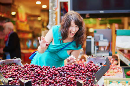 french woman: Cheerful happy young French woman selecting cherries on market in Paris, France Stock Photo
