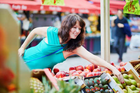 french woman: Beautiful French woman choosing ripe organic peaches and pears on a Parisian local market. Customer in food store, supermarket or hypermarket concept