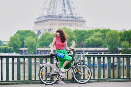 Enthousiaste jeune femme à bicyclette dans une rue de Paris, près de la tour Eiffel