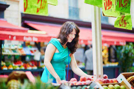 french woman: Beautiful French woman choosing ripe organic peaches on a Parisian local market. Customer in food store, supermarket or hypermarket concept