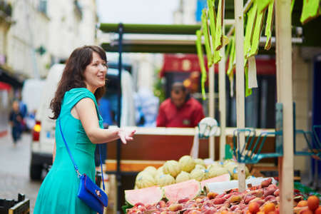 french woman: Beautiful French woman negotiating the price on a Parisian local market. Customer in food store, supermarket or hypermarket concept