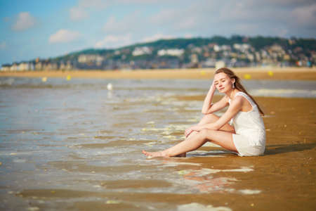 normandy: Beautiful young woman enjoying her vacation by ocean or sea, sitting near water edge at sunset. People on sea vacation concept Stock Photo