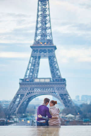 fiancee: Young romantic couple near the Eiffel tower at early morning in Paris, France
