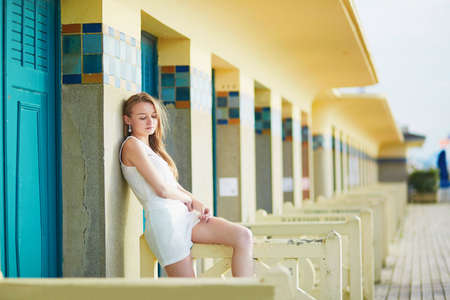 normandy: Beautiful young woman sitting near beach cabins in Deauville, Normandy, Northern France, Europe