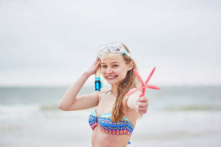 snorkelling: Happy young woman in bikini with snorkelling equipment and pink starfish enjoying summer vacation holidays by ocean or sea. Beach, travelling and people concept Stock Photo