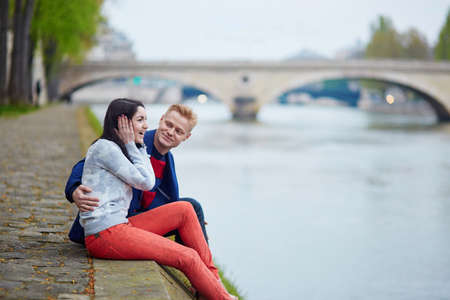 Happy couple sitting on the bank of the Seine in Paris. Tourists enjoying their vacation in France. Romantic date or traveling couple concept
