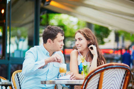 Romantic loving couple drinking coffee and cocktails in an outdoor cafe. Tourists on vacation or during their honeymoon in Paris, France Stock Photo