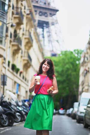 french woman: Cheerful young French woman walking with coffee to go and baguette (white bread) on a street of Paris, Eiffel tower in the background