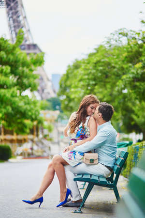 Romantic loving couple having a date near the Eiffel tower, sitting on a bench in green summer park.