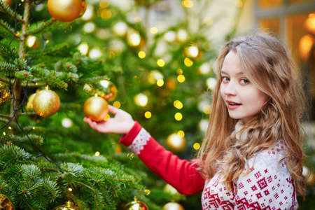 decorating christmas tree: Cheerful young woman decorating Christmas tree with golden balls