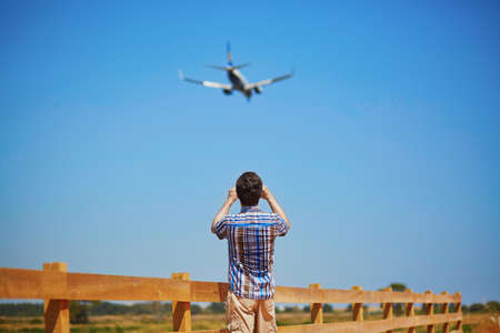 glide: Man is looking at the glide path and landing plane or taking a photo of it.