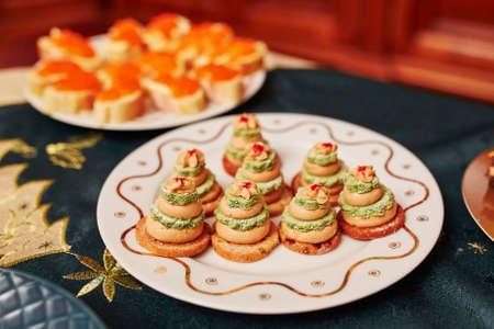 Set de table pour le dîner de Noël avec de délicieux amuse-gueules - sandwichs foie gras sous forme de petits arbres de Noël