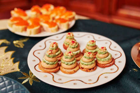 amuse: Table set for Christmas dinner with delicious appetizers - fois gras sandwiches in form of little Christmas trees Stock Photo