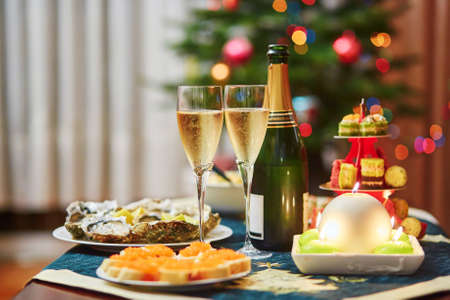Set de table pour le dîner de Noël avec des apéritifs délicieux, des huîtres et du champagne. Décoré arbre de Noël dans l'arrière-plan