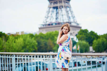 french woman: Beautiful French woman walking near the Eiffel tower. Tourist in Paris on summer vacation