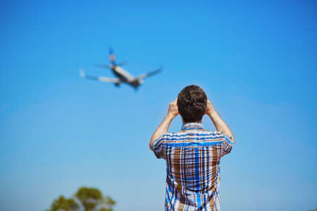 glide: Man is looking at the glide path and landing plane or taking a photo of it. Aircraft spotting concept