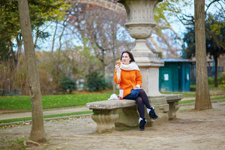 Cheerful young woman in orange coat walking on a street of Paris with hot beverage to go photo