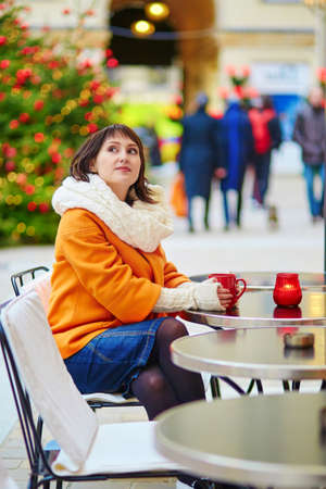Cheerful young woman in orange coat in Paris decorated for Christmas, drinking coffee, tea or hot chocolate in an outdoor cafe photo