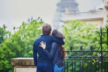 Happy young couple in front of the Eiffel tower. Tourists in Paris Stock Photo